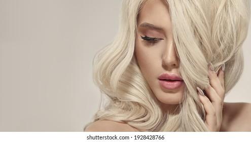 Portrait de luxe d'une femme européenne sexy aux cheveux blonds magnifiques sur fond beige, image en gros plan avec place pour texte libre.