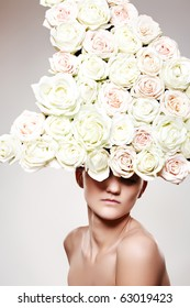 Luxury portrait of young woman model with a big white rose hat in a fashion model pose. Creative wedding accessories, headwear, flowers. Bride looking.
