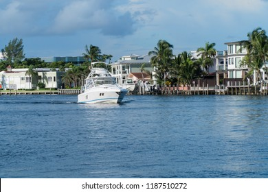 Luxury power boat yacht sailing up river waterway with luxury homes in background along shore line. Day time summer exterior photo