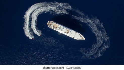 A luxury private motor yacht and two jetski drawing a circle