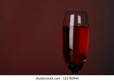 luxury red wine in champagne flute on grey background