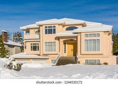 Luxury residential house with front yard in snow. North American family house on winter sunny day