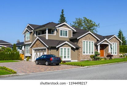 Luxury residential house with green hedge on side and green lawn in front. Suburban family house with double garage and car parked on paved driveway
