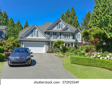 Luxury residential house with green hedge and landscaping in front. Family house surrounded by trees with blue sky background. Suburban house with double garage and car parked on concrete driveway.