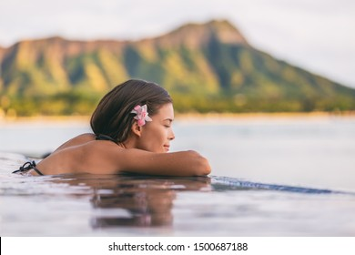 Luxury resort wellness pampering spa lifestyle Asian woman relaxing in infinity swimming pool of outdoor hotel on Waikiki beach, Honolulu, Hawaii travel.