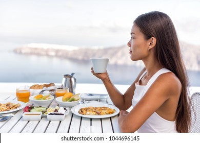 Luxury resort woman drinking coffee at breakfast table looking at Mediterranean sea view from hotel outdoor restaurant balcony or room. Tourist eating food relaxing, healthy brunch.