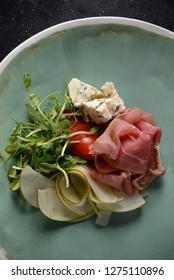 A luxury restaurant appetizer dish with prochutto ham, dor ble cheese, apple and micro green, flat lay