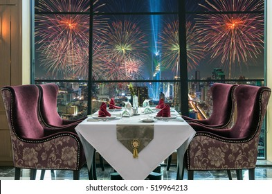 Luxury restaurant set over windows glass of Top view of Bangkok Cityscape at night with Multicolor Firework Celebration, Mahanakhon, dicut each elements