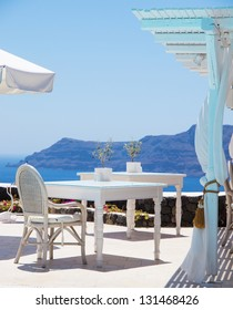 A luxury restaurant situated in the town of oia on the greek island of santorini with a view of volcano in the distance.