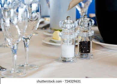 Luxury restaurant table with plates and glasses set. Close up crop, focus on glass salt shaker and whole pepper mill. Shallow depth of field