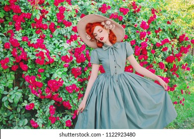 Luxury retro girl with red lips in mint dress on a beautiful summer background. Stylish woman. Fashionable summer clothes. Young luxury redhead model in a hat on a background of a bush of roses.