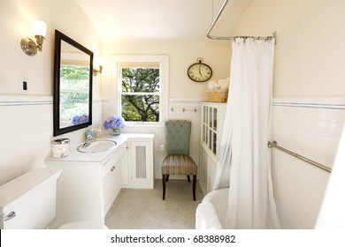 Luxury Romantic Bathroom With Iron Tub And Cream Color And Purple Flowers.