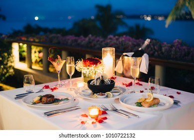 Luxury romantic candlelight dinner table setup for couple in ocean view restaurant on Valentine's day with Champaign & wine glasses and beautiful food decoration.