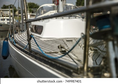 A luxury sailing yacht in a harbor in the summer with golden sunlight shining upon the boat