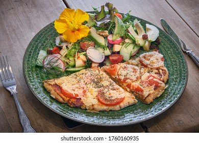 Luxury salad with homemade cheese and tomato pizza on a rustic green plate on a wooden table