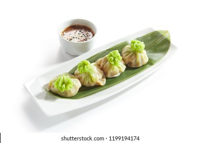 Luxury Serving Vegetarian Dim Sum, Dimsum or Momos on a Banana Leaf with Spicy Sauce Isolated on White Background. Macro Photo of Chinese Restaurant Wontons or Dumplings Close Up