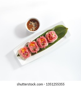Luxury Serving Vegetarian Dim Sum, Dimsum or Momos on a Banana Leaf with Spicy Sauce Isolated on White Background. Chinese Restaurant Wontons or Dumplings Top View