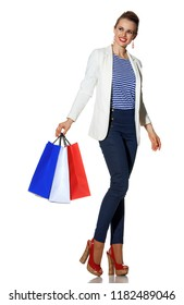 Luxury Shopping. The French way. Full length portrait of happy young woman in white jacket isolated on white with shopping bags painted in the color of the French flag looking at copy space