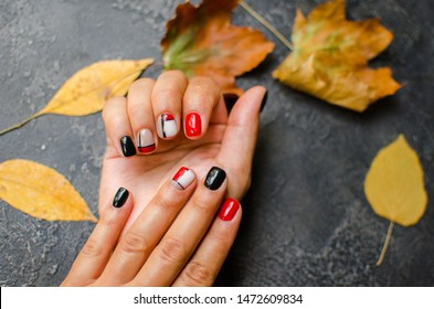 Luxury short manicure on a dark wooden background. cozy autumn nails. Red and black color nails.