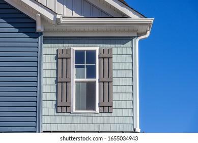 Luxury single family home natural wood look rough shake finish vinyl Bermuda blue shake and shingle, pacific blue horizontal siding, double pane window with dark shutters, snow trim, beaded corner