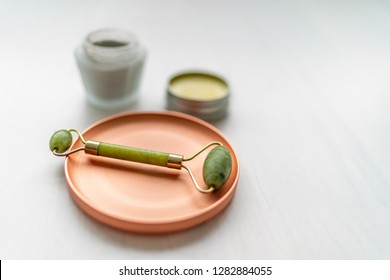 Luxury skincare korean beauty products - creams, balm and mud mask jars with jade stone face roll massager - Facial roller massaging therapy.