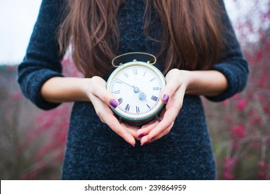luxury slim pretty woman holding alarm clock in front of her