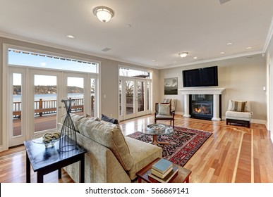 Luxury spacious family room interior with wall of glass doors leading out to spacious deck and facing the lake, polished hardwood floor and cozy sitting area with fireplace . Northwest, USA