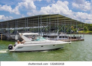 Luxury speedboat with rolled floatie on back on lake in summer passing by covered boat dock with more fancy boats and No Wake Zone sign