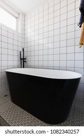 Luxury stand alone black bathtub in a dully tiled bathroom