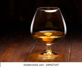Luxury still life with glass of cognac, on a wood background. Front view with copyspace. Close up shot
