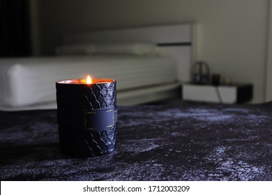 The luxury stylish design aroma scented glass candle is lighting in the white bedroom on the dark marble texture table