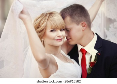 luxury stylish happy caucasian blonde bride with groom on the background amazing architecture of lviv