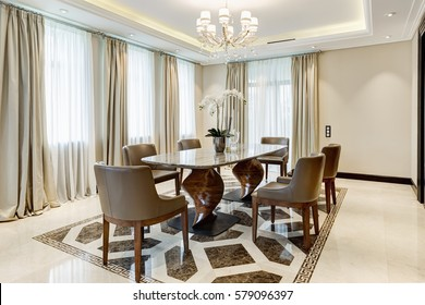 Luxury and stylish interior. Empty dining room with flowers on big wooden table in center and chairs around. Big windows and crystal chandelier in center of ceiling.