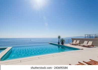 Luxury swimming pool and blue water at the resort with beautiful sea view.