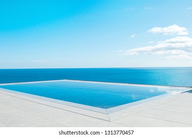 Luxury swimming pool in front of the sea. Swimming pool with beautiful sea and sky view.