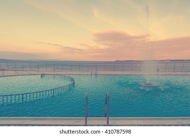 Luxury swimming pool in front of sea at during sunset.
