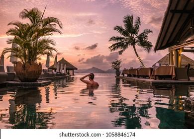 Piscina de lujo en complejo tropical, vacaciones relajantes en las islas Seychelles. La Digue, joven al atardecer en la piscina