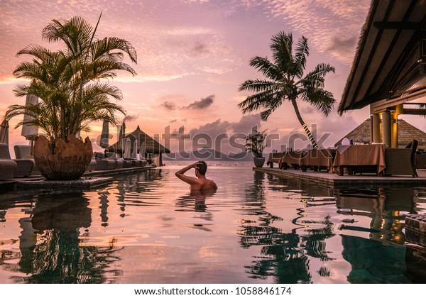 Piscine de luxe dans un complexe tropical, vacances relaxantes dans les îles Seychelles. La Digue, Jeune homme au coucher du soleil par piscine