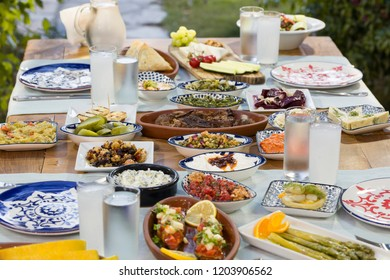 Luxury table with plate of fish, meat, pickles, antipasto, aubergine, appetizers, cheese, mezze, salad, octopus, raki and ouzo. Copy space for text area.