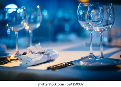 Luxury Table setting focus on the glass blue background.