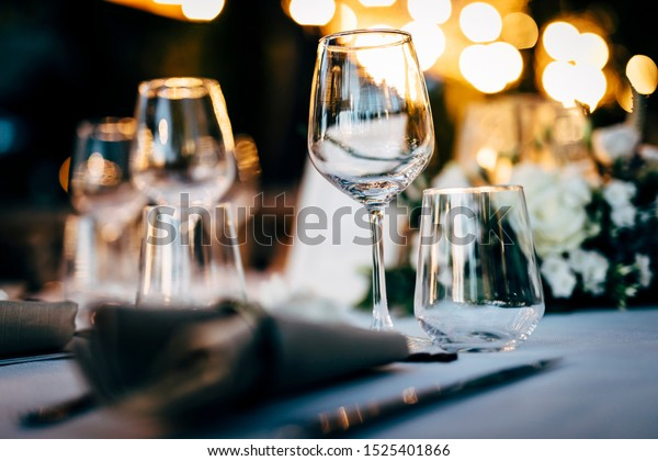 Luxury table settings for fine dining with and glassware, beautiful blurred  background. For events, weddings.  Preparation for holiday dinner night. props for weddings, birthdays, and celeb