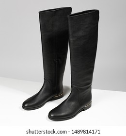 Luxury women's tall black autumn and winter boots, over the knee boots, stand on gray-white background with shadow