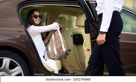 Luxury taxi service, chauffeur opening car door for female passenger, travel