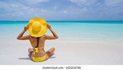 Luxury Travel. Beach woman enjoying serene luxury vacation relaxing under the sun looking at perfect turquoise water and ocean at tropical getaway paradise. Girl bikini model from the back sunbathing.