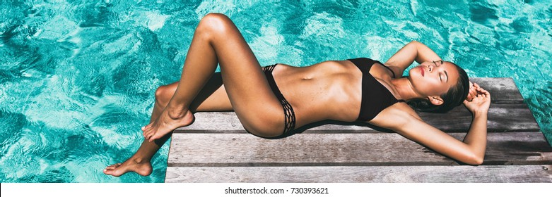Luxury travel bikini girl vacation banner. Asian woman sun tan over idyllic ocean water in Bora Bora Tahiti, French Polynesia island. Panoramic horizontal crop of exotic holiday.