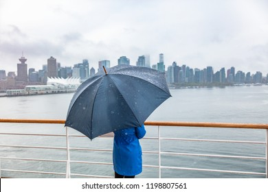 Luxury travel cruise woman leaving port watching city skyline of Vancouver under the rain with umbrella. Ship voyage destination in autumn.