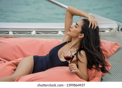 Luxury travel on the yacht. Young woman Wearing a black swimsuit and drinking wine enjoying party on boat deck sailing the sea.