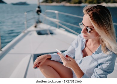Luxury travel on the yacht. Young happy woman using smartphone on boat deck sailing the sea. Yachting and technology.