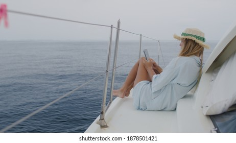 Luxury travel on the yacht. Young woman reading or writing text or messages on smartphone.