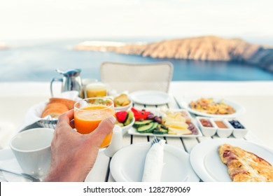 Luxury travel resort breakfast in room service at fancy hotel restaurant with amazing balcony view over Santorini island, Oia, Greece. Europe vacation food selfie. Man drinking morning orange juice.